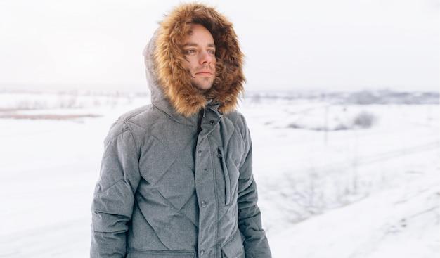 Uomo che indossa giacca invernale grigia con cappuccio acceso nella neve d'inverno Foto Premium