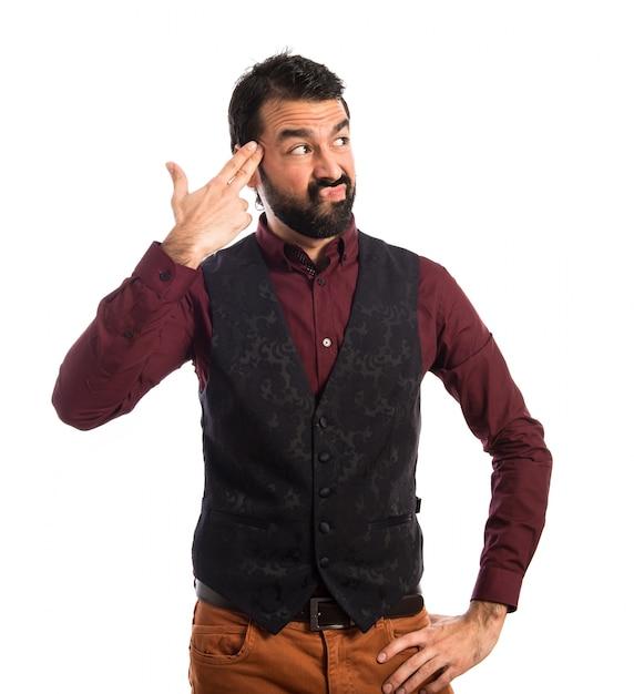 Uomo che indossa il panciotto facendo il gesto suicida Foto Gratuite