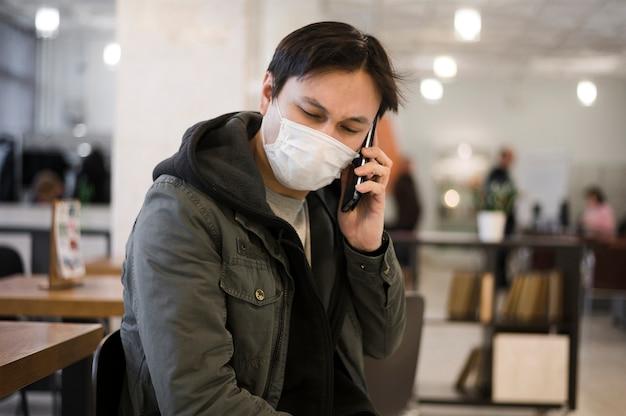 Uomo che indossa una maschera medica e parlando al telefono Foto Gratuite