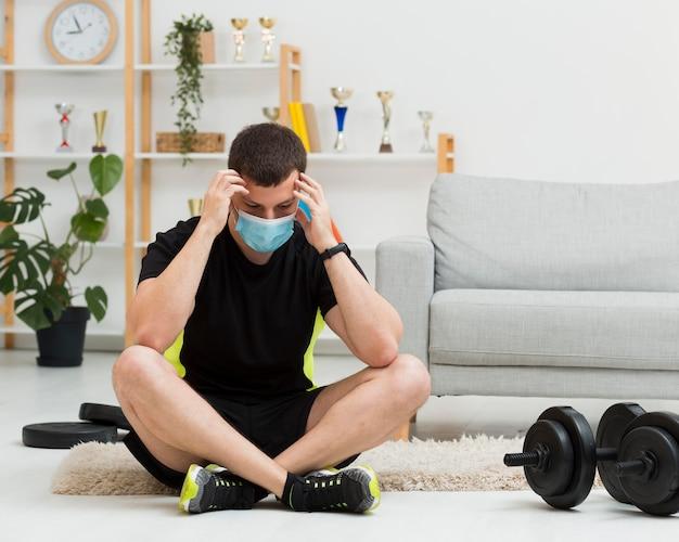 Uomo che indossa una maschera medica mentre indossa abiti sportivi Foto Gratuite