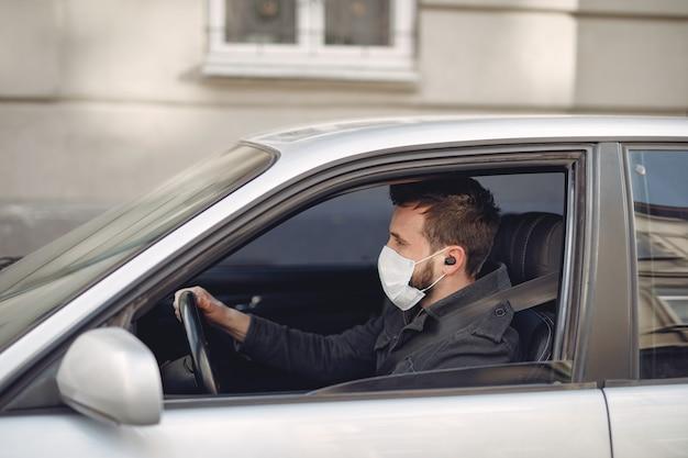 Uomo che indossa una maschera protettiva seduto in una macchina Foto Gratuite