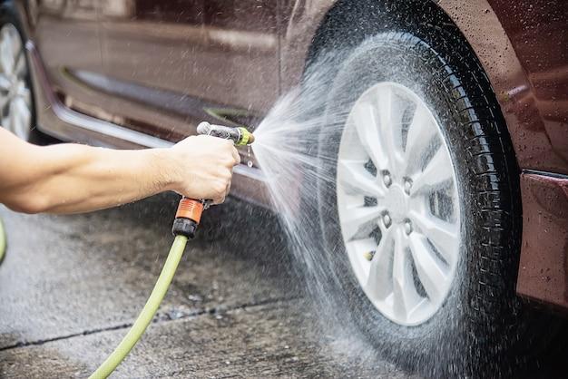 Uomo che lava auto usando shampoo e acqua Foto Gratuite
