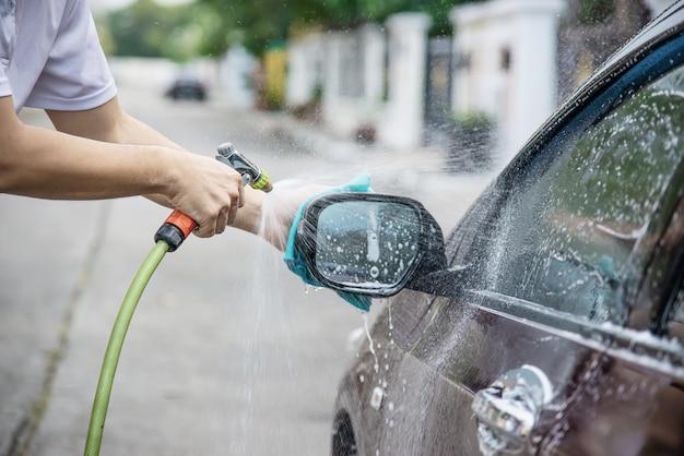 Uomo che lava la macchina usando acqua a getto Foto Gratuite