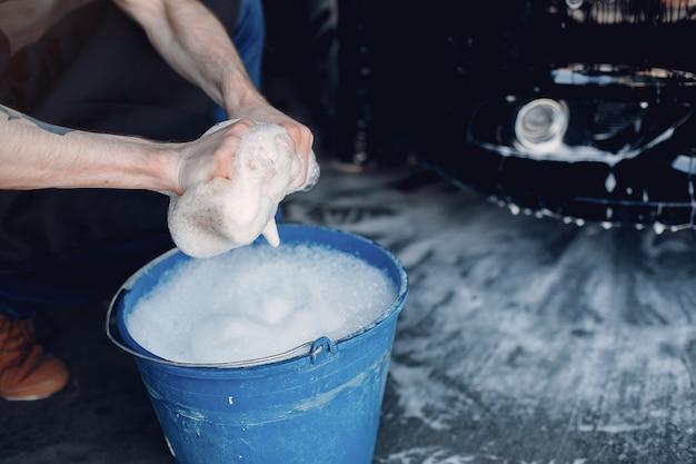 Uomo che lava la sua auto in un garage Foto Gratuite