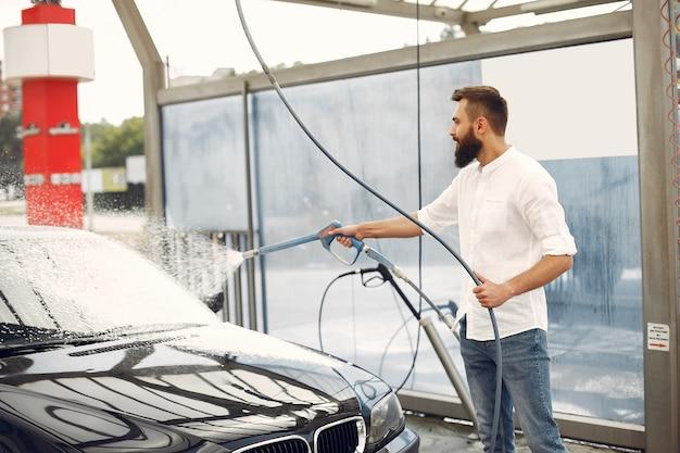 Uomo che lava la sua auto in una stazione di lavaggio Foto Gratuite
