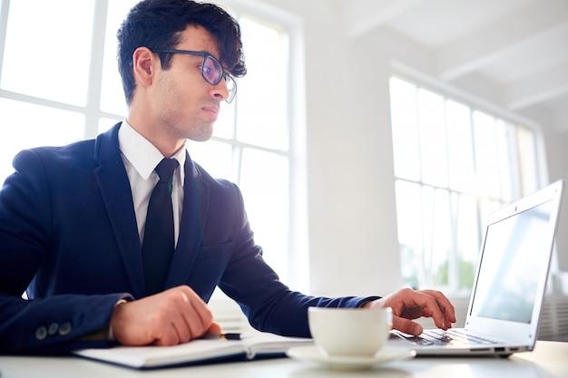 Uomo che lavora con il computer portatile all'ufficio Foto Gratuite