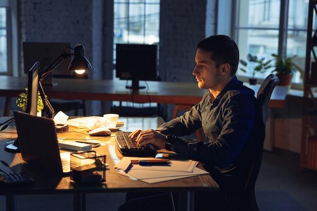 Uomo che lavora in ufficio da solo Foto Gratuite