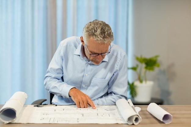 Uomo che lavora su un progetto alla sua scrivania Foto Premium