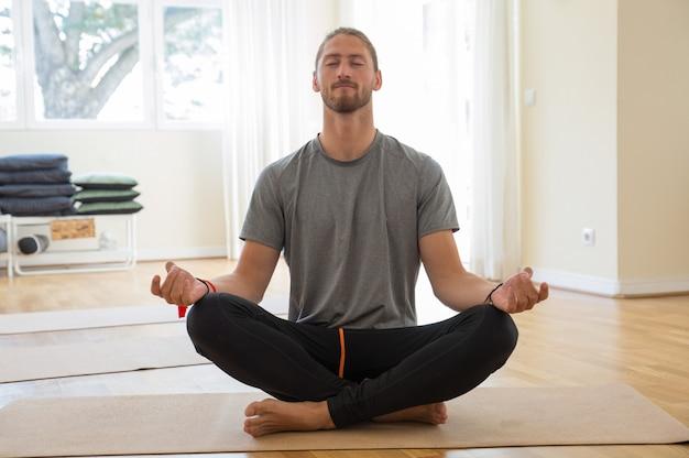 Uomo che medita e che si tiene per mano nel gesto di mudra in classe Foto Gratuite