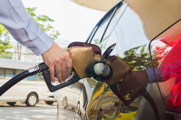 Uomo che mette benzina nel suo auto in una pompa di benzina Foto Gratuite