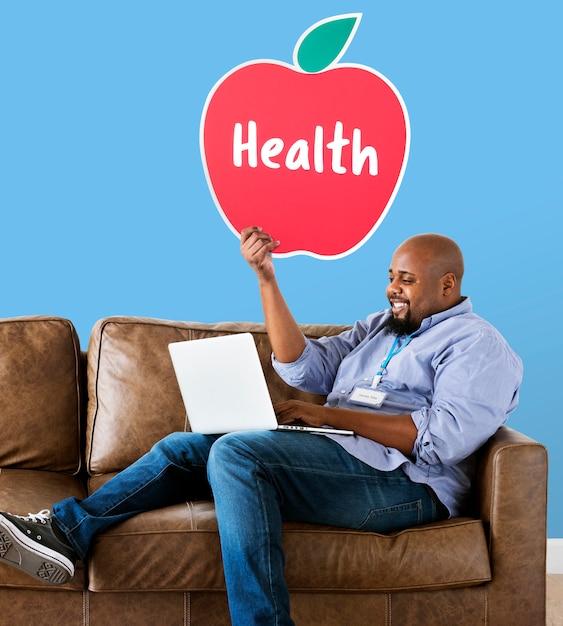 Uomo che mostra icona mela sana sul divano Foto Gratuite