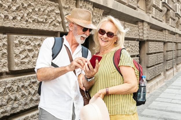 Uomo che mostra qualcosa sul telefono della donna mentre sorride Foto Gratuite