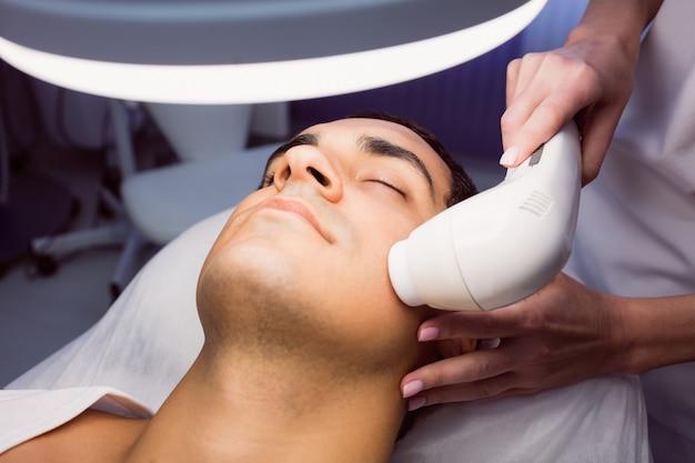 Uomo che ottiene un massaggio facciale alla clinica Foto Gratuite
