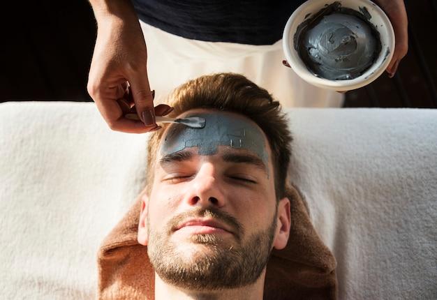 Uomo che ottiene una maschera di fango in una spa Foto Gratuite