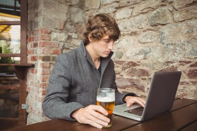 Uomo che per mezzo del computer portatile Foto Gratuite