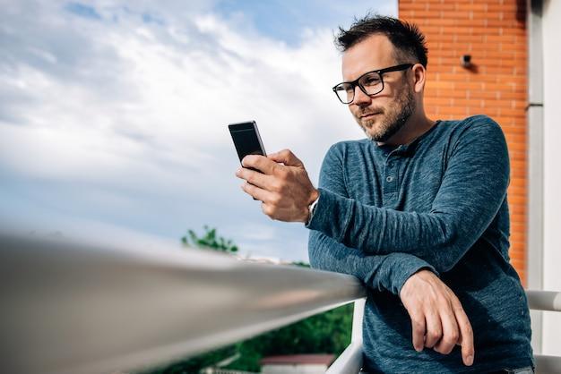 Uomo che per mezzo del telefono sulla terrazza Foto Premium