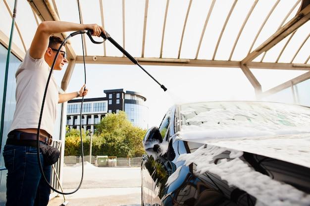 Uomo che per mezzo di un bastone per spruzzare acqua sull'automobile Foto Gratuite