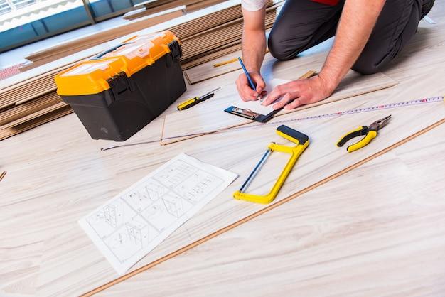 Uomo che pone la pavimentazione laminata nella costruzione Foto Premium