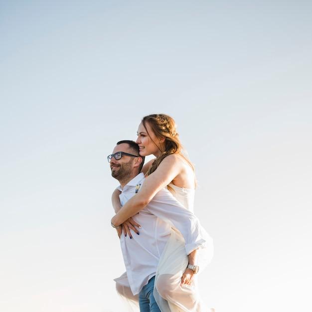 Uomo che porta la sua ragazza sulla schiena in una spiaggia contro il cielo blu Foto Gratuite