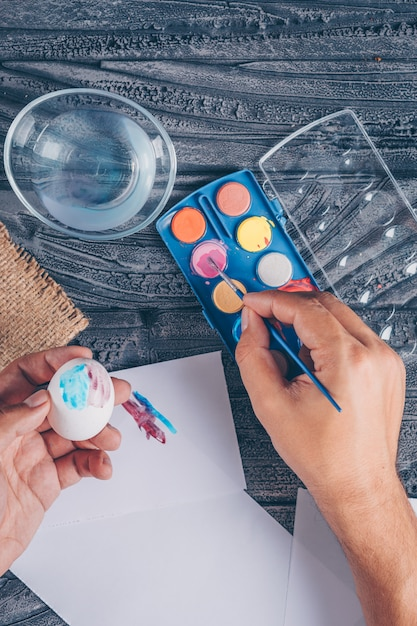 Uomo che produce un uovo di pasqua con vernice su fondo di legno scuro Foto Gratuite