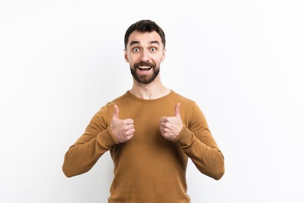 Uomo che propone e che dà i pollici in su Foto Gratuite