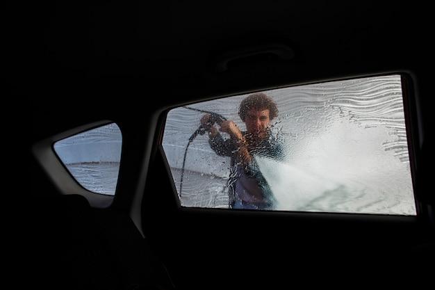 Uomo che pulisce con acqua un finestrino della macchina Foto Gratuite
