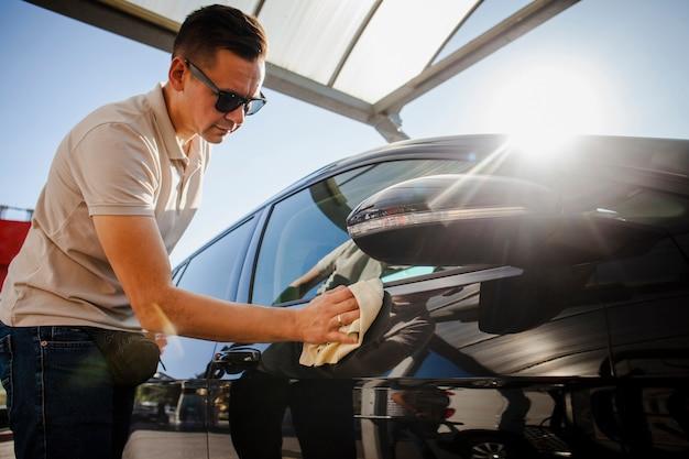 Uomo che pulisce con cura un'auto nera Foto Gratuite