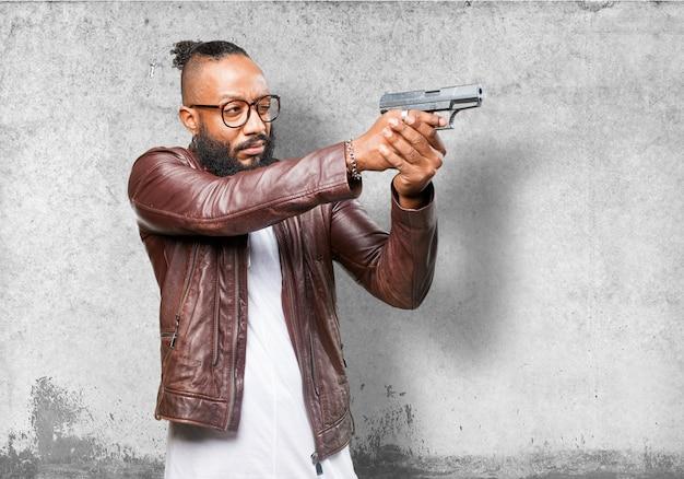 Uomo che punta con una pistola scaricare foto gratis