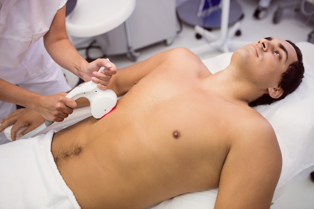 Uomo che riceve un trattamento di epilazione laser Foto Gratuite