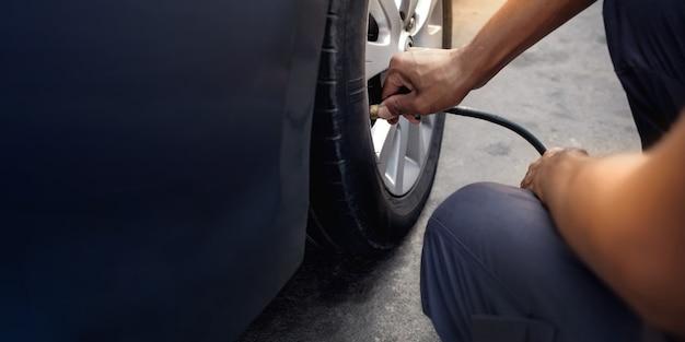 Uomo che riempie l'aria nella ruota. driver dell'automobile che controlla pressione e manutenzione dell'aria Foto Premium