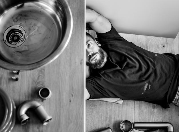 Uomo che ripara il lavello della cucina Foto Premium