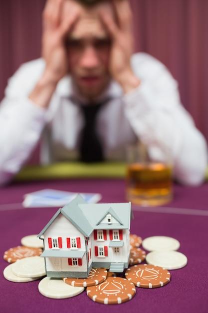 Uomo che rischia la sua casa al gioco del poker Foto Premium