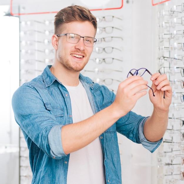 Uomo che sceglie i nuovi vetri all'optometrista Foto Gratuite