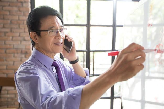 Uomo che scrive su lavagna e che parla sul telefono Foto Gratuite