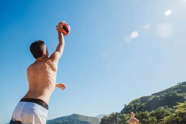 Uomo che serve pallavolo in una giornata di sole Foto Gratuite