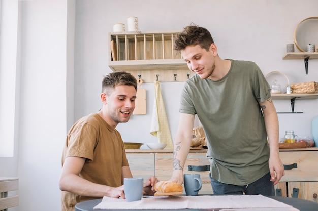 Uomo che serve pane e caffè sul tavolo di legno Foto Gratuite
