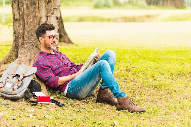 Uomo che si appoggia sotto i libri di lettura dell'albero nel parco Foto Gratuite