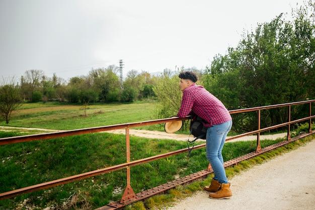 Uomo che si appoggia sulla ringhiera guardando la natura Foto Gratuite