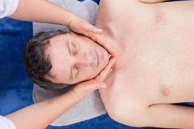 Uomo che si rilassa sul lettino da massaggio che riceve massaggio facciale Foto Premium