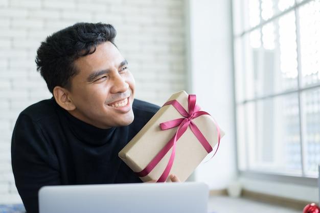 Uomo che sorride e che tiene regalo con il computer portatile per venerdì nero e lunedì cibernetico Foto Premium
