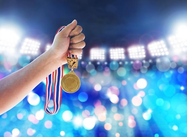 Uomo che sostiene una medaglia d'oro contro, vincere il concetto. Foto Premium