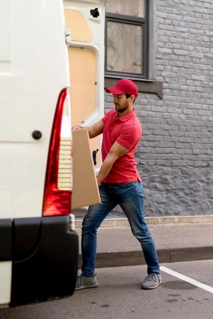 Uomo che spinge i pacchetti in auto Foto Gratuite