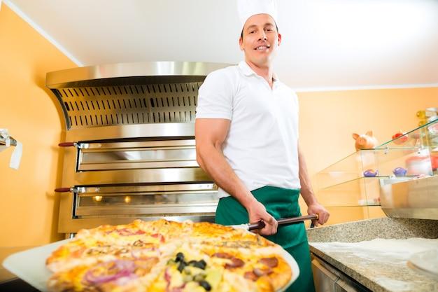 Uomo che spinge la pizza finita dal forno Foto Premium