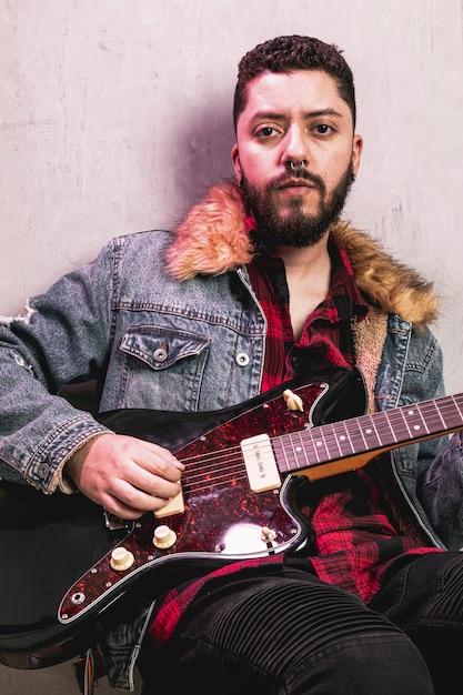 Uomo che suona la chitarra e guardando il fotografo Foto Gratuite