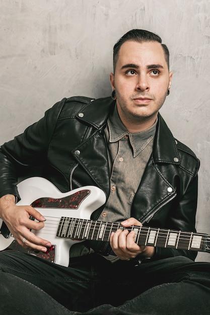Uomo che suona la chitarra e guardando lontano Foto Gratuite