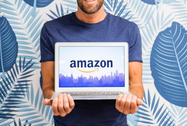 Uomo che tiene il portatile con il sito di amazon Foto Gratuite