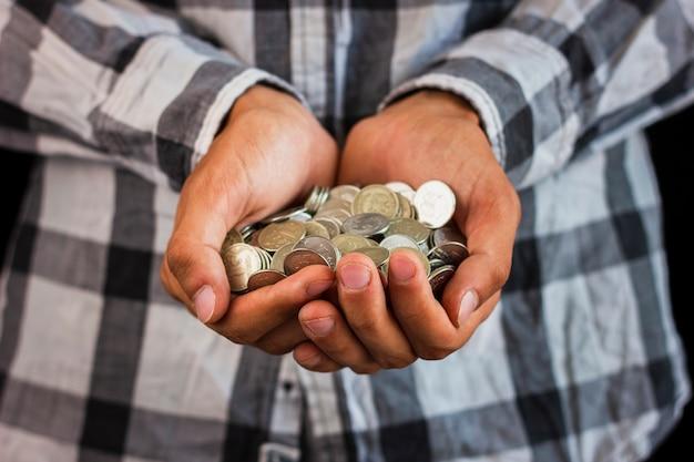Uomo che tiene in mano risparmiando monete Foto Gratuite