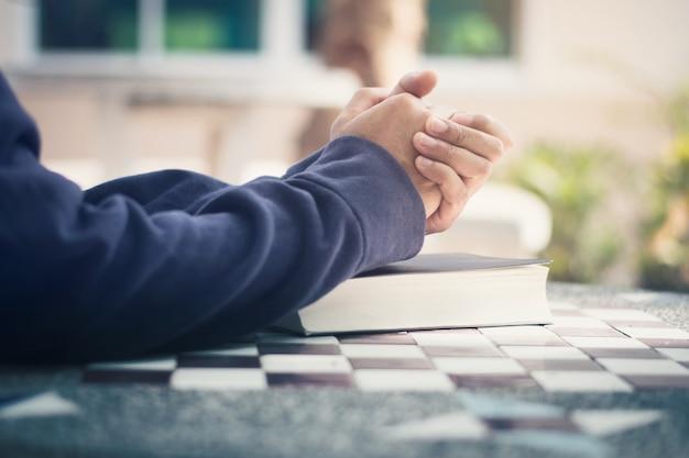 Uomo che tiene in mano una bibbia e prega Foto Premium