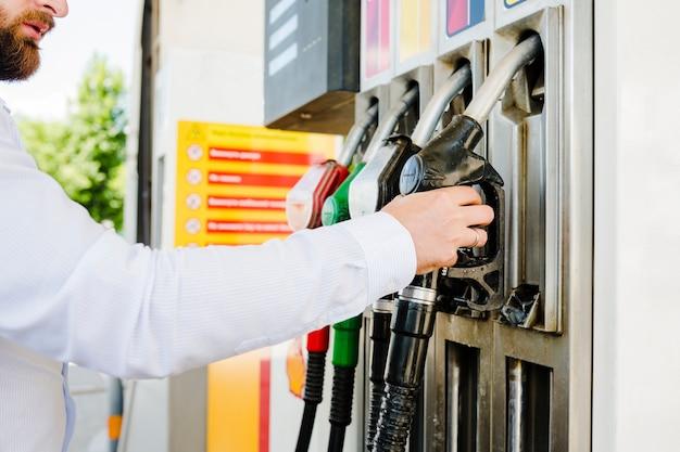 Uomo che tiene l'ugello di carburante in una stazione di benzina Foto Gratuite
