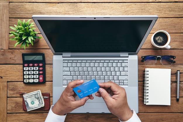 Uomo che tiene la carta di credito e utilizzando il computer portatile. Foto Premium